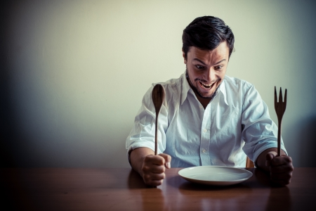young stylish man with white shirt eating in mealtimes behind a table photo