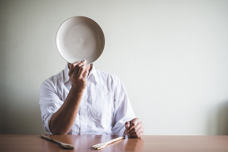 young stylish man with white shirt and dish in his face behind a table photo