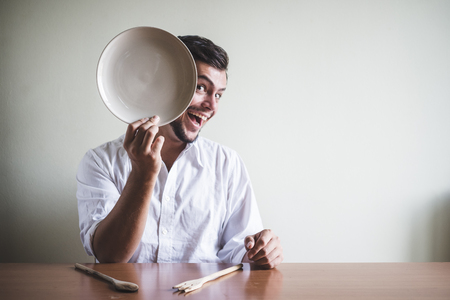 abstinence: young stylish man with white shirt and dish in his face behind a table