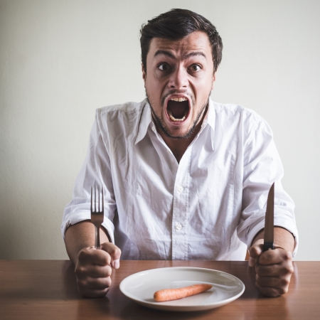 crazy man: young stylish man with white shirt eating carrot behind a table