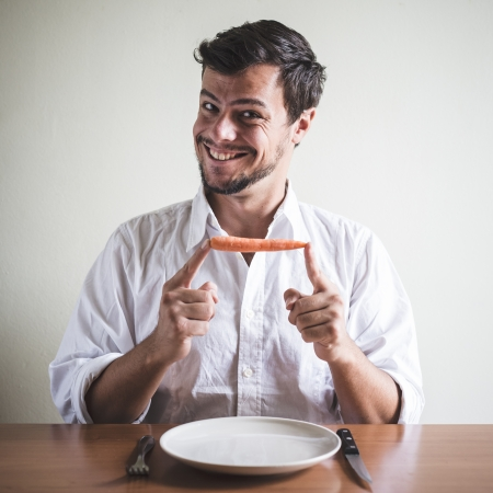 abstinence: young stylish man with white shirt eating carrot behind a table