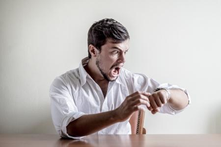 punctual: hombre con estilo joven con camisa blanca tiempo reloj detrás de una mesa Foto de archivo