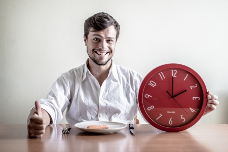 punctual: young stylish man with white shirt holding red clock behind a table
