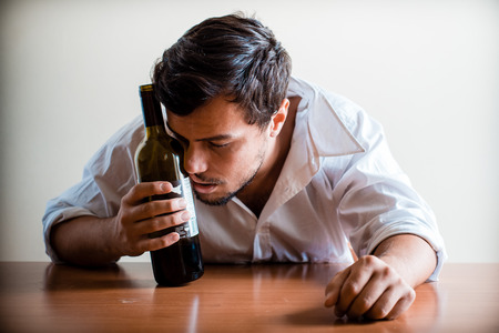 drunk young stylish man with white shirt behind a table photo