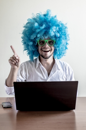 funny crazy young man with blue wig using notebook on the table photo