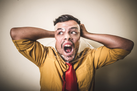 suffocating: suffocating man with the plastic on white background Stock Photo