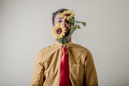 young stylish man with flowers on white background photo