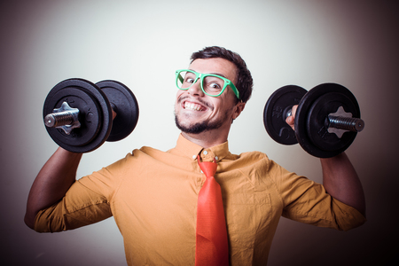 funny crazy young man weightlifting on gray background photo