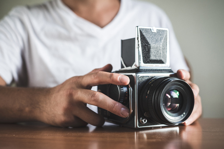 young stylish hipster man with old camera on the table at home photo