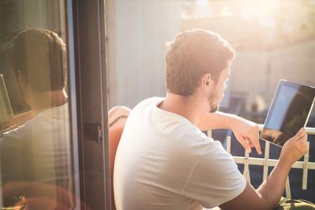 lifestyle: jonge stijlvolle hipster man met behulp van tablet op het huis balkon Stockfoto