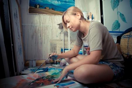 mooie blonde vrouw schilder in haar atelier Stockfoto