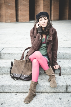 beautiful young woman on the phone in the city autumn photo