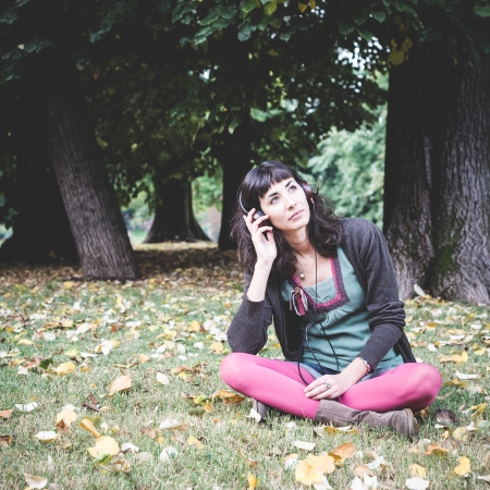 young beautiful woman listening to music at the park in autumn photo