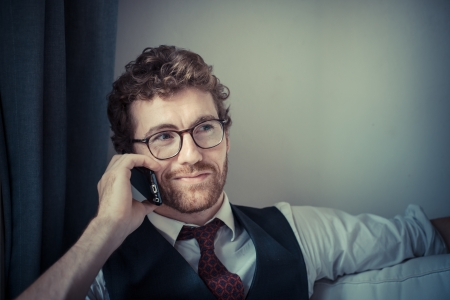 elegant attractive fashion hipster man on the phone at home photo