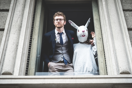 elegant attractive fashion hipster man with rabbit woman appeared at the window photo