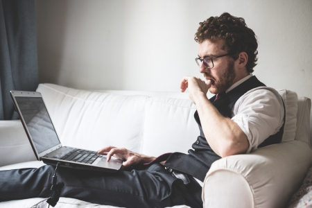 elegant attractive fashion hipster man using notebook at home Stock Photo