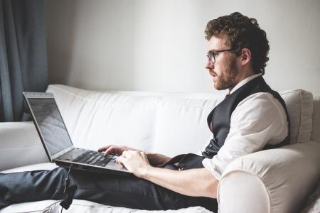 elegant attractive fashion hipster man using notebook at home Zdjęcie Seryjne