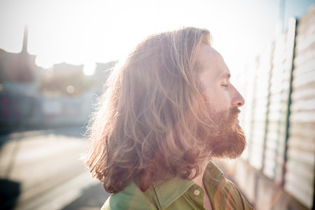 stylish hipster model with long red hair and beard lifestyle in the street Stock Photo