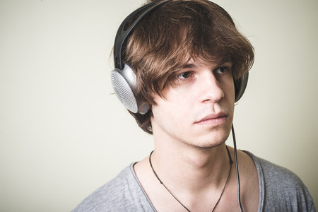 stylish young blonde hipster man listening to music on white background photo