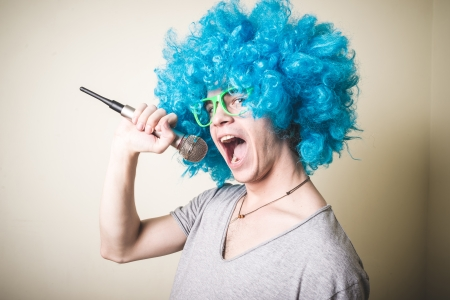 funny guy with blue wig singing on white background photo