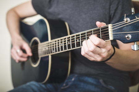 close up of hands playing guitar on white background photo