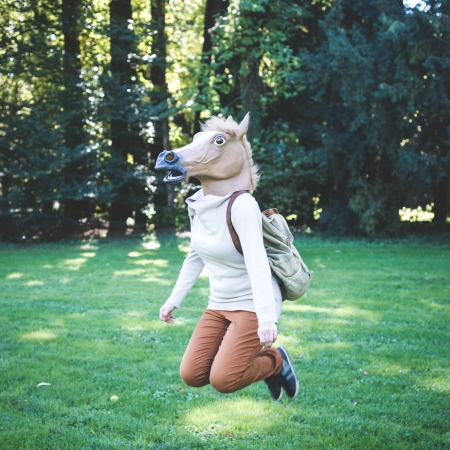 horse jumping: young hipster horse mask woman in the woodland autumn