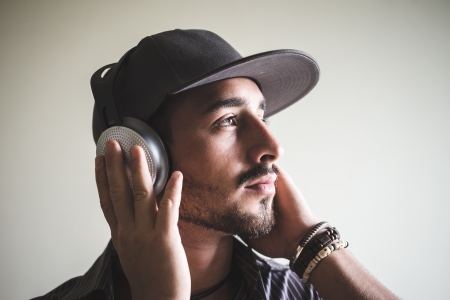 young stylish man listening to music on gray background photo