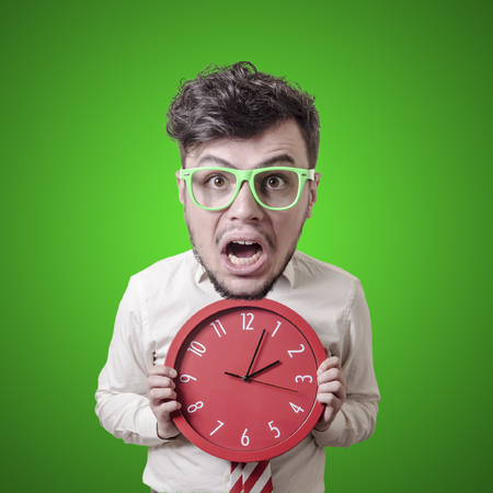 funny puppet business man holding clock on green background