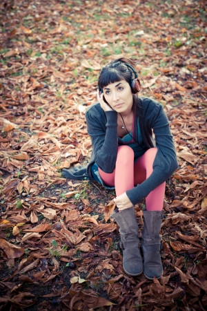 beautiful young woman listening to music in the city autumn photo