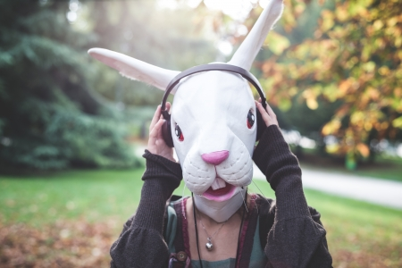 rabbit mask woman listening to music in the park autumn