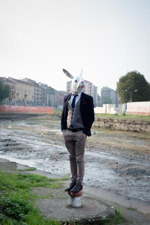 rabbit mask man in a desolate landscape river photo