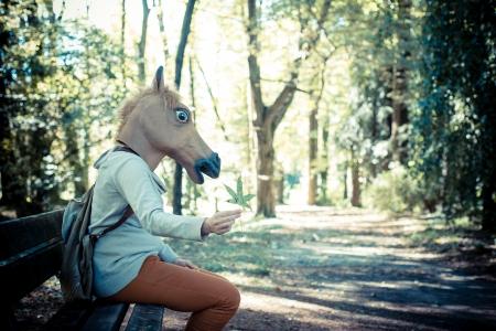 houtsoorten: jonge hipster paard masker vrouw in het bos herfst Stockfoto