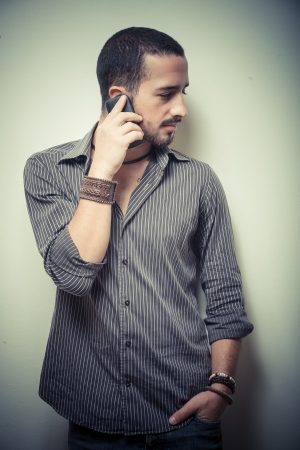 young stylish man on the phone on gray background photo