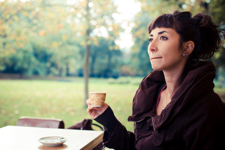 beautiful young woman drinking coffee in the city autumn photo