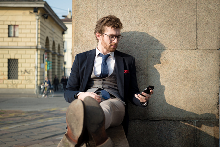 elegant attractive fashion hipster man on the phone in the city