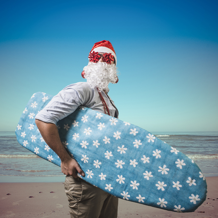 funny santa claus surfer beach on holiday photo