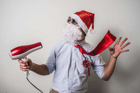 babbo natale: funny santa claus babbo natale with hairdryer on white background