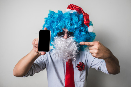 babbo natale: funny santa claus babbo natale using phone on white background Stock Photo