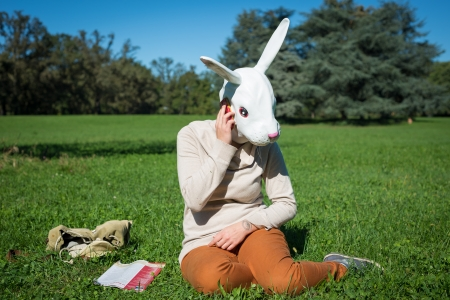 young hipster rabbit mask woman on the phone in autumn on the grass photo
