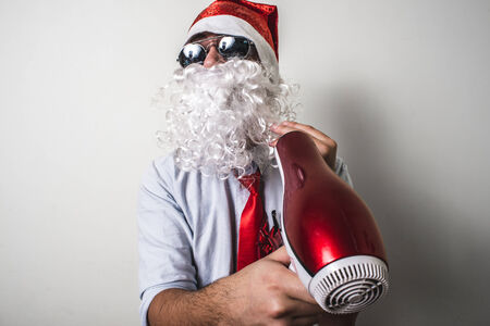 funny santa claus babbo natale with hairdryer on white background