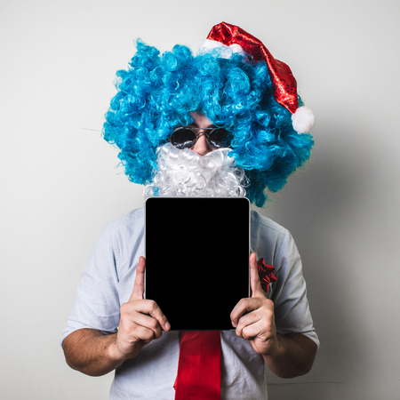 funny santa claus babbo natale using tablet on white background photo