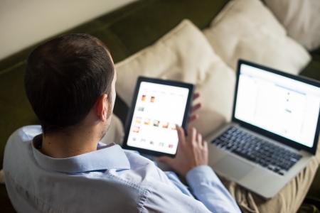 usando computadora: elegante hombre de negocios multimedia multitarea utilizando dispositivos en el hogar Foto de archivo