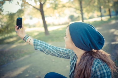 beautiful young blonde hipster stylish woman selfie in the park
