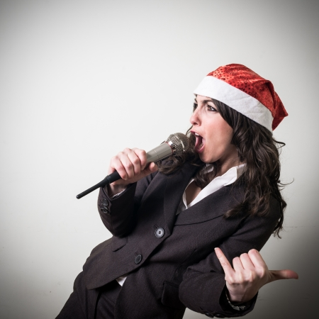christmas businesswoman singing with microphone on white background photo