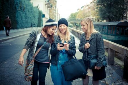 persone che parlano: tre amici donna al telefono in strada