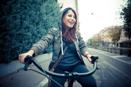 biker girl: beautiful red head womanon bike in the city