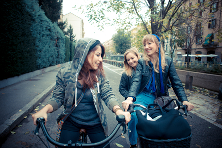 candid: three friends woman on bike in urban contest
