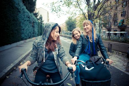 trois: trois amis femme � v�lo en contexte urbain Banque d'images
