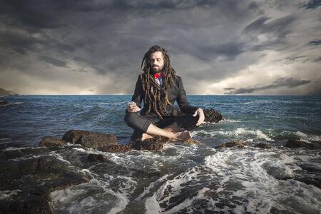 levitating: Stylish elegant dreadlocks businessman levitating in sea landscape Stock Photo