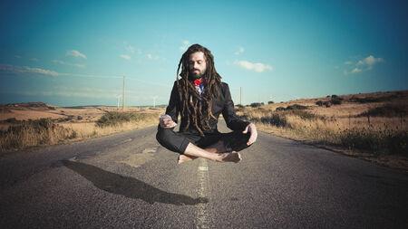levitating: Stylish elegant dreadlocks businessman levitating in a desolate road